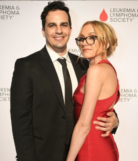 Kat Timpf wearing red dress and Cameron wearing Black suit attending a Cancer event.