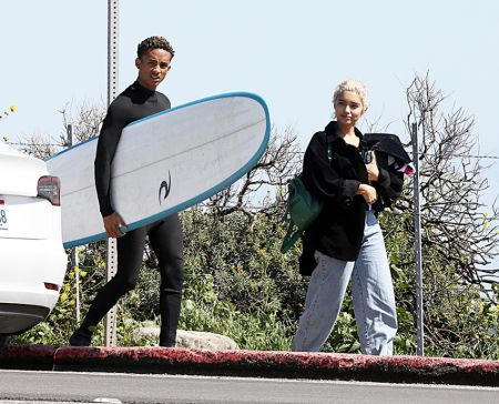 Jaden holding surfing board and a blonde girl walking alongside him.